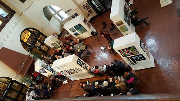 Erin Aldridge and Betsy Husby surrounded by art and audience. Photo credit: Patty Mester
