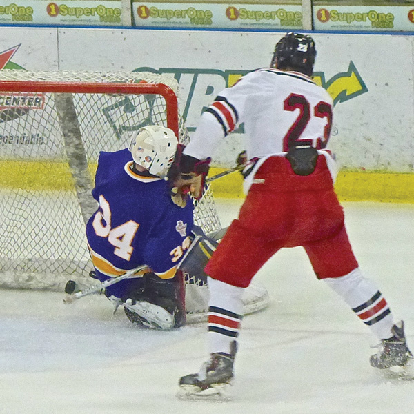 Duluth East's Ian Mageau followed through after tucking his shot through Cloquet-Esko-Carlton goaltender Eric Newman for a 3-0 lead. Photo credit: John Gilbert