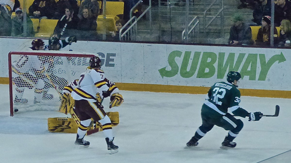 Bemidji freshman Zach Whitecloud peeled off to the right after scoring on UMD goalie Hunter Miska at 0:59 of the second overtime Friday night at AMSOIL Arena. Photo credit: John Gilbert