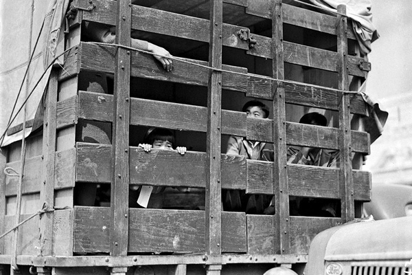 A truck packed with Japanese-American residents of San Pedro, California, leaves the city for a detention center on April 5, 1942.  Photo: Clem Albers
