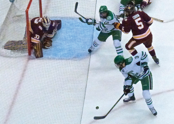 UMD goaltender Kasimir Kaskisuo, without his stick, was set to block a rebound try by North Dakota's Tucker Poolman in Friday's 4-2 victory. Photo Credit: John Gilbert