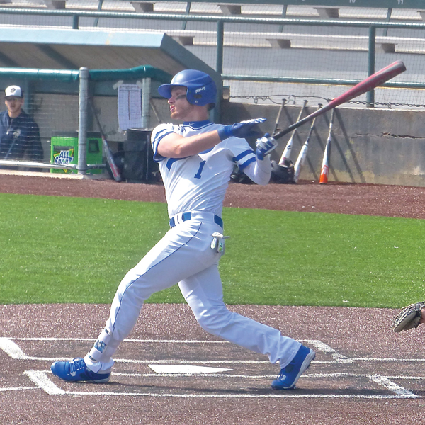 Junior catcher Trevor Bernsdorf drilled a base hit as St. Scholastica whipped North Central 14-1 at Wade Stadium in the Saints home opener. Photo credit: John Gilbert