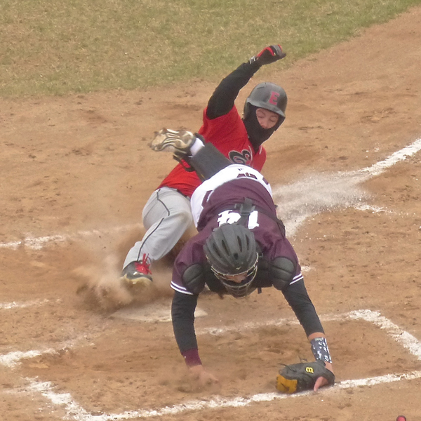 Nathaniel Benson, dressed for the chill, slid home in Duluth East's 3-run first inning of a 4-3 victory over Anoka. East's perfect record ended in the second game. Photo credit: John Gilbert