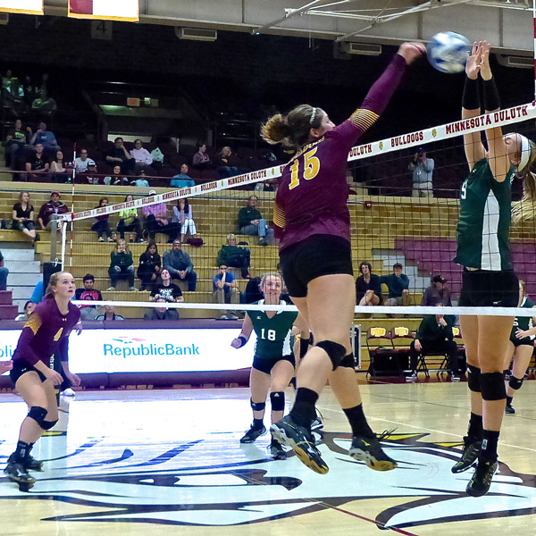 UMD senior Sydnie Mauch slams a kill through Bemidji State defenders, after a set-up by freshman Emily Torve, left. Photo credit: John Gilbert